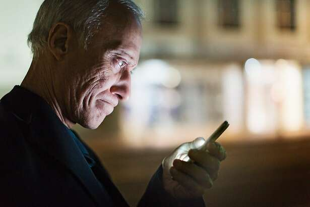 Mature man with his smartphone in the street at night.