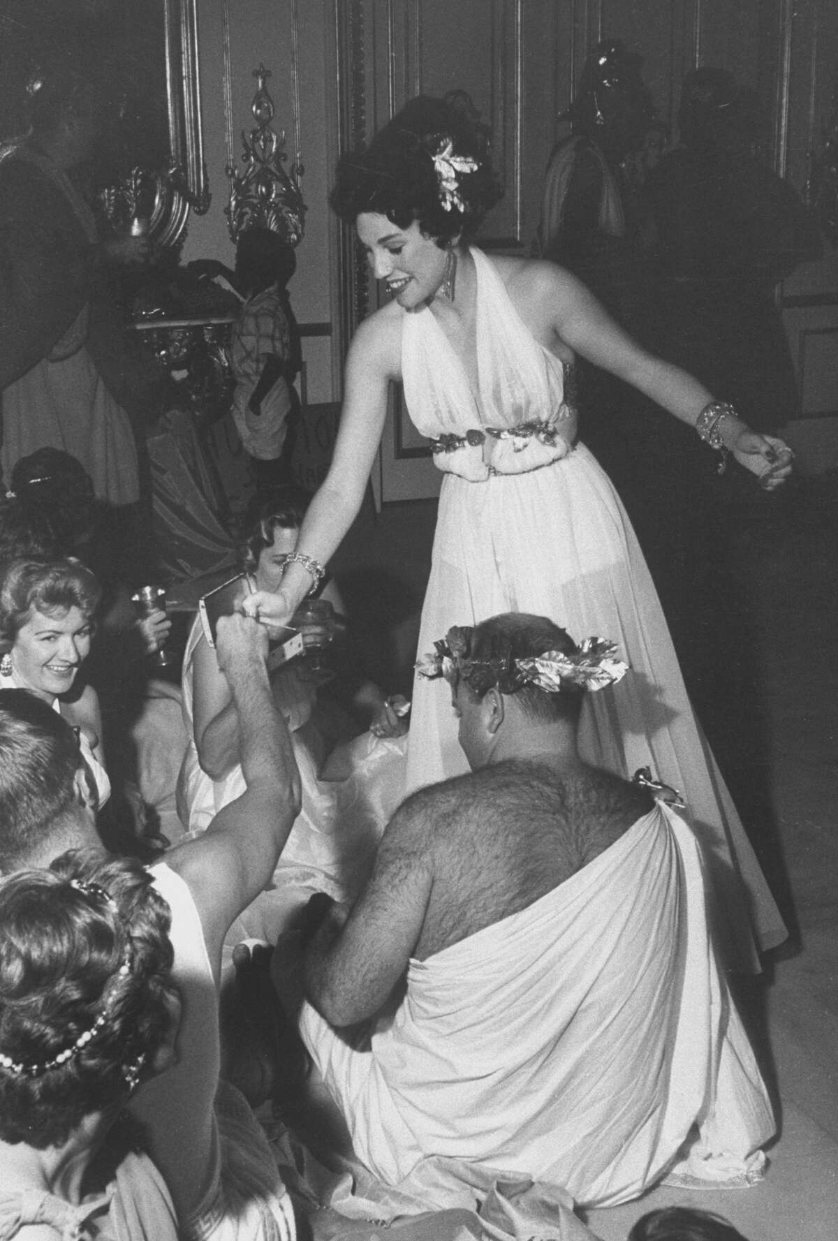 1959:American socialite and businesswoman Joanne King (later Herring) passes out lots to her guests in order to determine who will be mock 'burned at the stake' at a Roman-themed birthday in her honor held in her home, Houston, Texas, July 20, 1959.