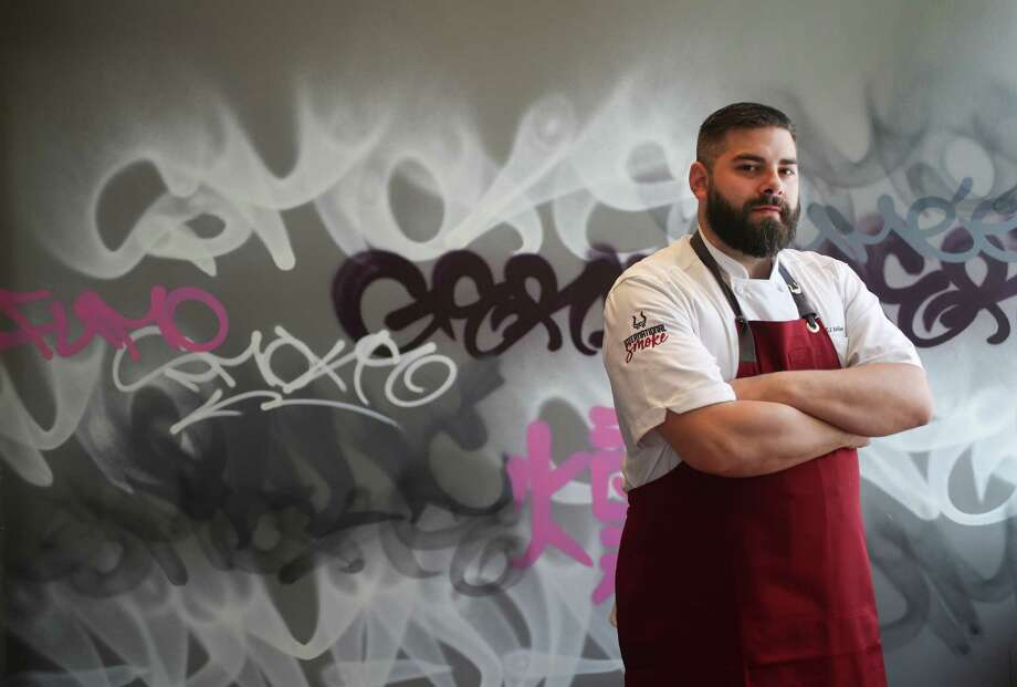 "International Smoke executive chef E.J. Miller poses by a wall painted with the word ""smoke"" in many different languages. International Smoke, described as an international approach to wood fire cooking, grilling and smoking, will open in Houston July 5 in CityCentre. Photo: Steve Gonzales, Houston Chronicle / © 2018 Houston Chronicle"