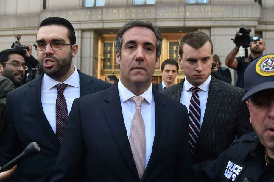 """(FILES) In this file photo taken on April 26, 2018 US President Donald Trump's personal lawyer Michael Cohen (C) leaves the US Courthouse in New York. Donald Trump's former personal lawyer, facing potential arrest in New York, has declared his first loyalty is to his family and the country, signaling a willingness to cooperate with prosecutors against the president. """"To be crystal clear, my wife, my daughter and my son, and this country have my first loyalty,"""" Michael Cohen told ABC News in an interview broadcast on July 2, 2018. / AFP PHOTO / HECTOR RETAMALHECTOR RETAMAL/AFP/Getty Images Photo: HECTOR RETAMAL, Contributor / AFP/Getty Images / AFP or licensors"""