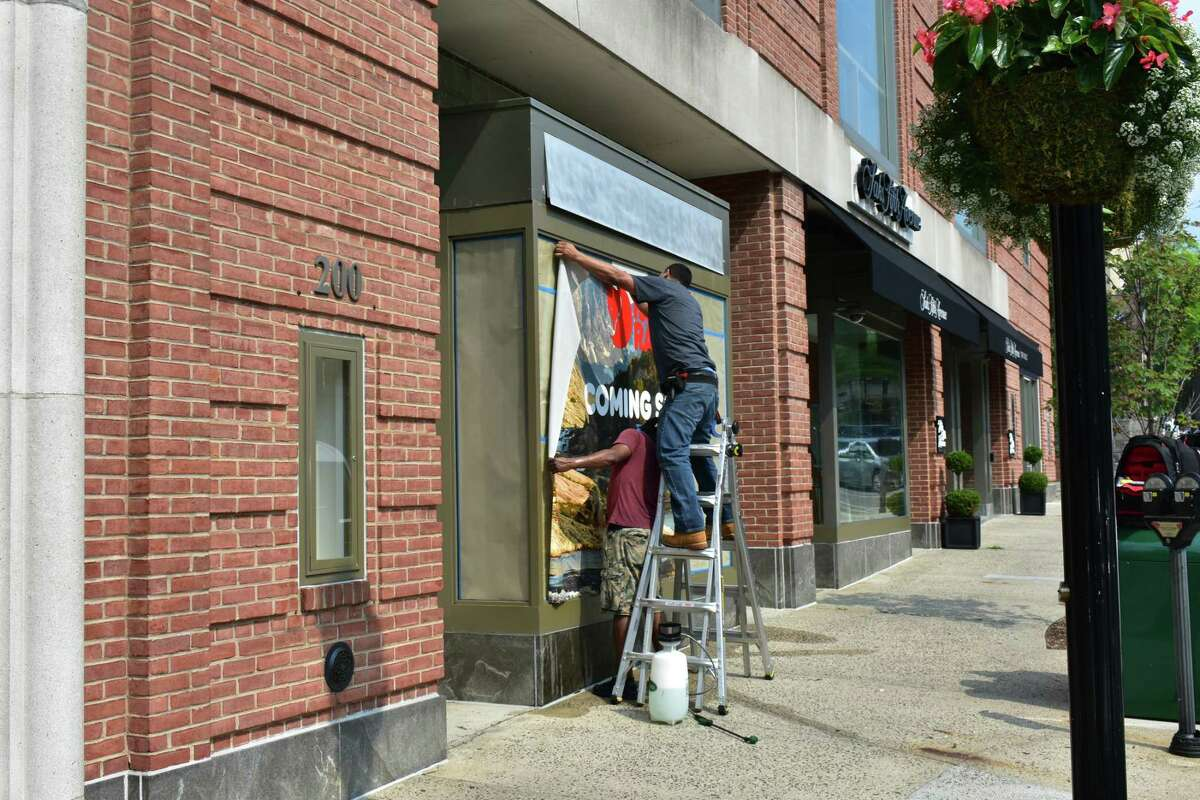 Workers hang retail outfitter Fjallraven's sign on Tuesday, July 3, 2018, at 200 Greenwich Ave. in Greenwich, Conn.