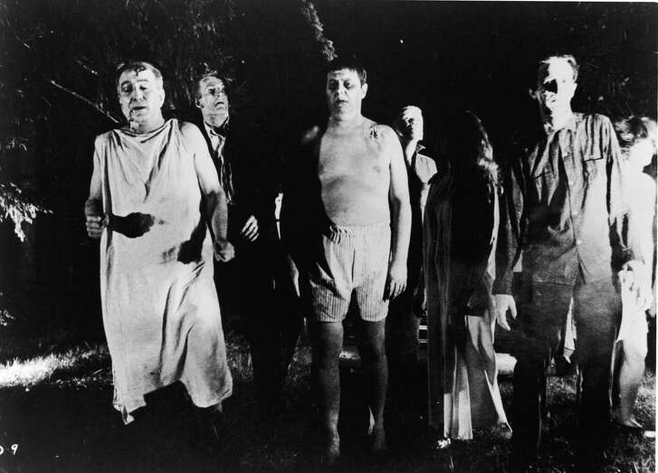 """A line of undead """"zombies"""" walk through a field in the film, """"Night Of The Living Dead,"""" directed by George Romero."""
