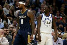 All-star big man DeMarcus Cousins, left, will be joining Draymond Green and the defending champion Warriors after he stunned the NBA universe by agreeing to a one-year contract with Golden State.