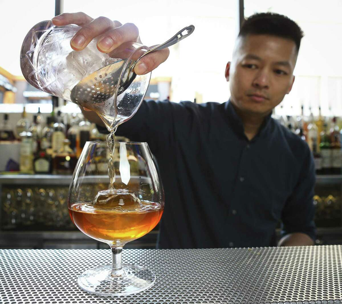 Gee Lee, the lead bartender at Yauatcha at The Galleria, makes one of the restaurants signature cocktails, the Elemental Fashion, behind the bar.
