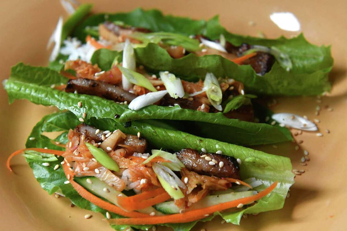 Korean pork belly tacos includes pork belly, romaine lettuce, rice, carrot, scallion, cucumber, bean sprouts, sesame seeds, and kimchi at Caroline Barrett's home on Wednesday, June 27, 2018 in Delmar, N.Y. (Lori Van Buren/Times Union)