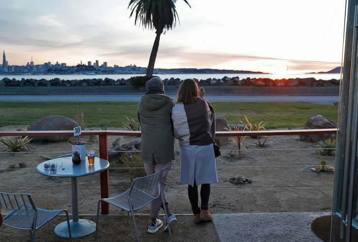 A couple watches the sunset at MerSea Restaurant on Treasure Island in San Francisco, Calif., on Monday, March 5, 2018. MerSea is a new restaurant  (made from shipping containers) on Treasure Island with a spectacular view of the city.