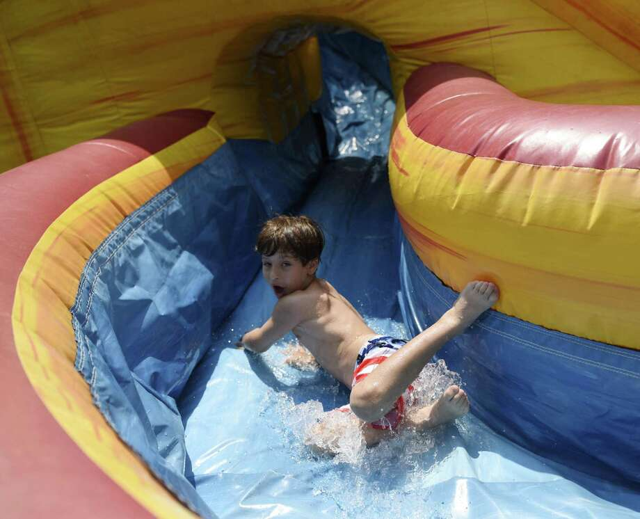 Maier B., 6, speeds down a water slide at Corbin's Crusaders summer day camp on the Greenwich Catholic School campus in Greenwich. The camp, for kids ages three to 14, is up to eight weeks long running June 25 through August 10 for kids in Fairfield County, Westchester County and New York City. Participants play a variety of sports and activities including swimming, tennis, color wars, archery, skateboarding, baseball gaga ball and more. Photo: Tyler Sizemore / Hearst Connecticut Media / Greenwich Time