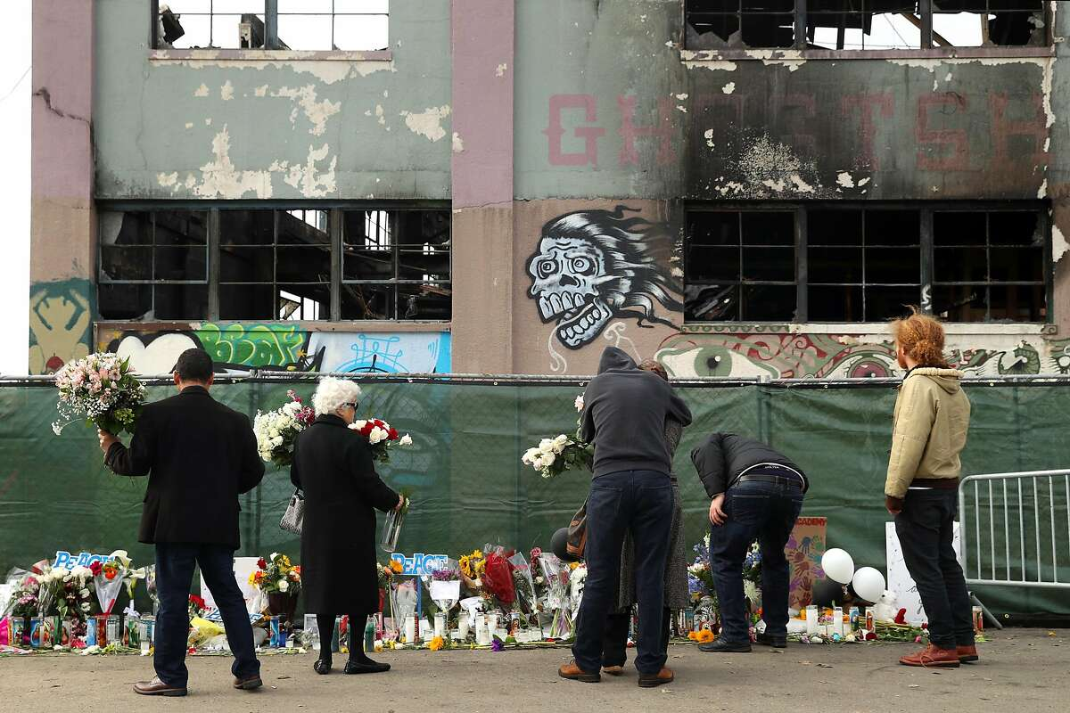 Family members of a Ghost Ship warehouse fire victim lay flowers at the scene on 31st Avenue in Oakland, Calif., on Monday, December 12, 2016.