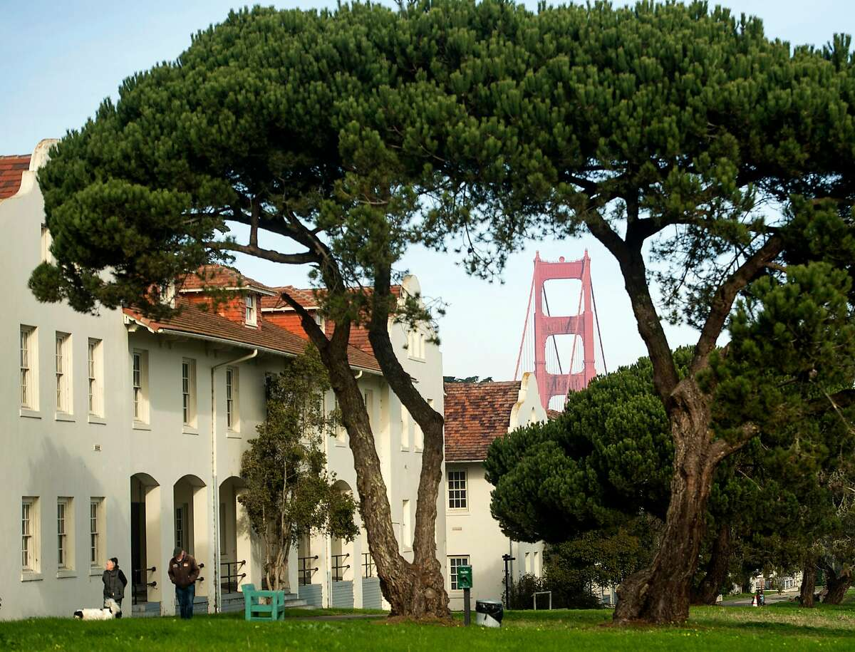 The Golden Gate Bridge rises behind buildings at Fort Scott in the Presidio on Wednesday, Jan. 17, 2018, in San Francisco. The Presidio Trust hopes to find a developer to revitalize the area.
