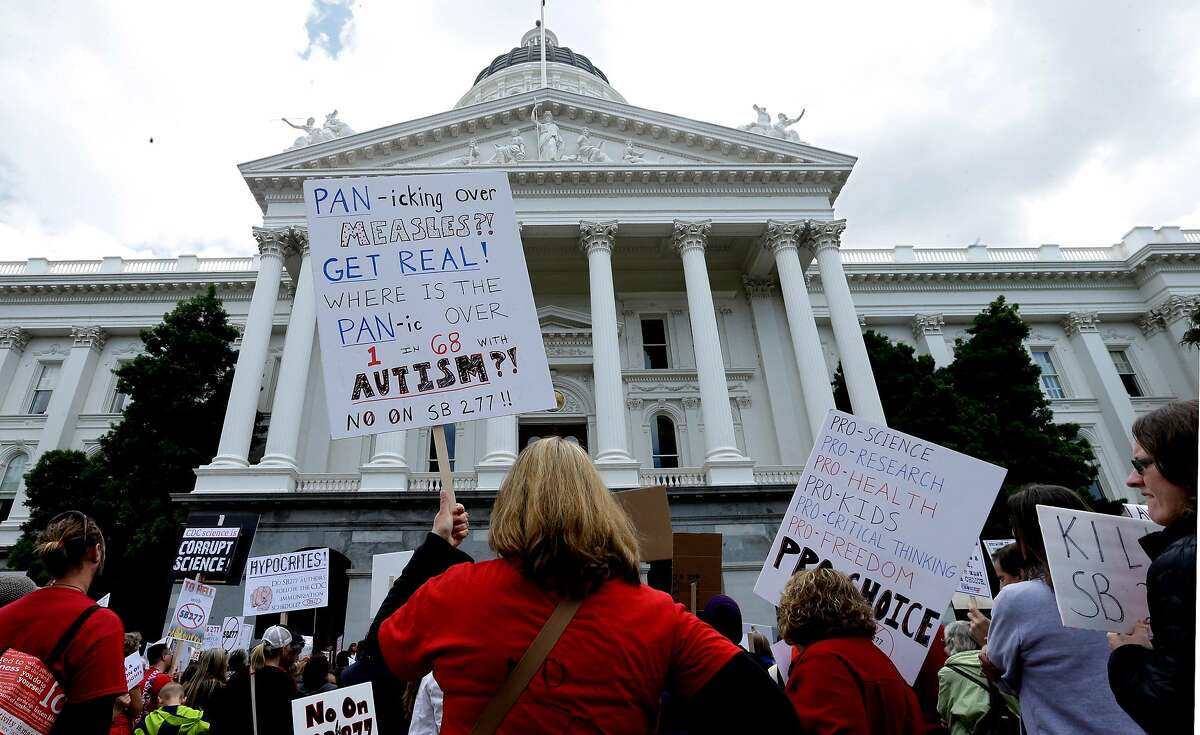 Kelly Trutter, back to camera, joined others protesting against a measure requiring California schoolchildren to get vaccinated, at a Capitol rally in Sacramento, Calif., Wednesday, April 8, 2015. The bill SB277 by Sen. Richard Pan, D-Sacramento, and Sen. Ben Allen, D-Santa Monica, will be heard by the California Senate Health committee Wednesday. If approved by the Legislature and signed by the governor, parents could no longer cite personal beliefs or religious reasons to send unvaccinated children to private and public schools unless a child�s health is in danger. (AP Photo/Rich Pedroncelli)
