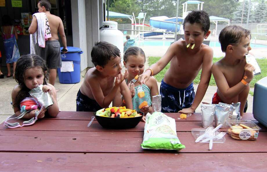 Fiona O'Leary, 3, left, her brother Ronan, 6, friend Bryan Scully, 10, James O'Leary, 8, and Ben Scully, 7, enjoy fruit and drinks as they wait behind the pool at Tashua Knolls in Trumbull, Conn., on Tuesday, July 3, 2018. Thunder closed the pool causing hot kids and adults searching for something else to keep cool. Photo: Christian Abraham / Hearst Connecticut Media / Connecticut Post