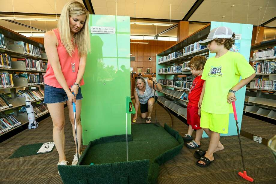 Alissa Brogdon (from left) lines up a putt on the 8th hole as her mother, Rhona Harris of Schertz, and sons Ames Brogdon, 6, and Rote Brogden, 9, wait for their turns during the 3rd Annual Tee Off for the Library at the Schertz Public Library, 798 Schertz Parkway, on Saturday, June 23, 2018. The mini golf fundraising event raised funds this year for new picnic tables and benches in the Library courtyard. Photo: Marvin Pfeiffer / San Antonio Express-News / Express-News 2018