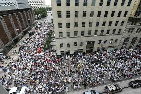 "Protestors fill Walker and Travis Streets in Houston as they make their way to U.S. Sen. Ted Cruz's office during an immigration rally on Saturday, June 30, 2018. Rallies were held across the nation calling on federal agencies to reunite families separated at the border under Trump's ""zero tolerance"" policy, as well as calling for the abolishment of ICE. (Elizabeth Conley/Houston Chronicle via AP)"