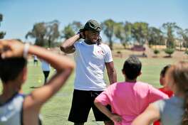 Najee Harris talks with kids during the Purpose Filled Youth Outreach leadership camp at Los Medanos College in Pittsburg, Calif., on Saturday, June 30, 2018. The camp was an athletic style camp whose purpose was faith-based leadership skills building.