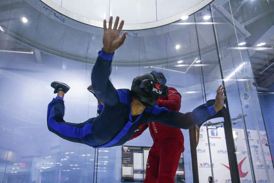iFly instructor Ivan Buznego, right, helps lead instructor Marlon Mahoney, left, float in the wind tunnel while wearing a virtual reality headset for a 13,000 foot virtual free fall Monday, June 25, 2018. The headset plays a 360 degree video of professional skydivers jumping over the Swiss Alps, Dubai or Hawaii while customers float in the iFly wind tunnel. (Michael Ciaglo / Houston Chronicle) Photo: Michael Ciaglo, Houston Chronicle / Houston Chronicle / Michael Ciaglo