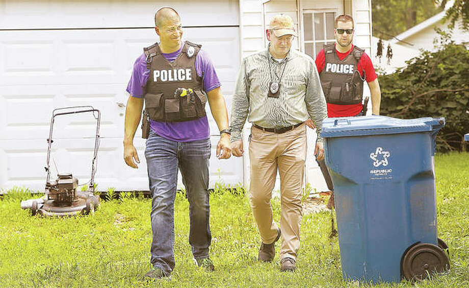 "Alton Police officers and an Alton Building and Zoning Department inspector walk away from a house Tuesday at 616 Oakwood Road in Alton after declaring it ""unfit for human habitation"". Photo:       John Badman 