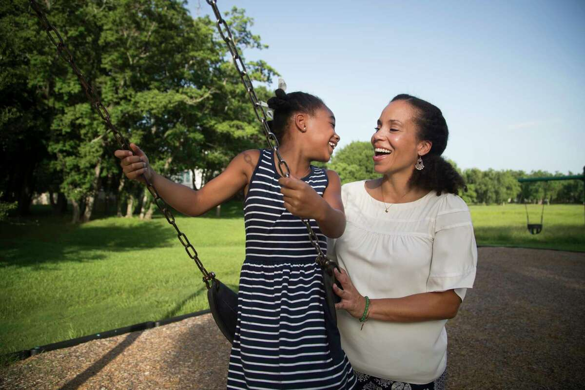 Tia Norman and her daughter Kennedy Bradford, 7, play at a park near their home. Norman has created a business, Joy to the Table, that provides families with tools to create a joyful environment at the dinner table.