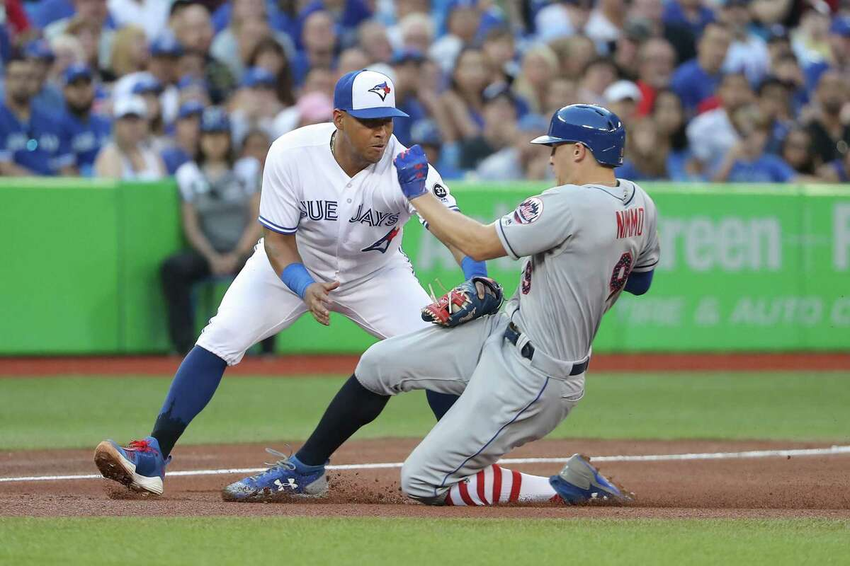 TORONTO, ON - JULY 3: Brandon Nimmo #9 of the New York Mets is tagged out attempting to steal third base by Yangervis Solarte #26 of the Toronto Blue Jays in the fifth inning during MLB game action at Rogers Centre on July 3, 2018 in Toronto, Canada. (Photo by Tom Szczerbowski/Getty Images)