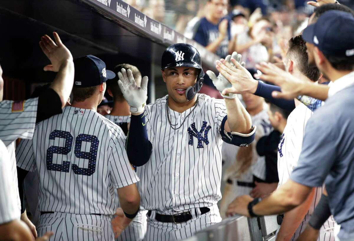 New York Yankees' Giancarlo Stanton celebrates with teammates after hitting a two-run home run during the eighth inning of a baseball game against the Atlanta Braves on Tuesday, July 3, 2018, in New York. The Yankees won 8-5. (AP Photo/Frank Franklin II)