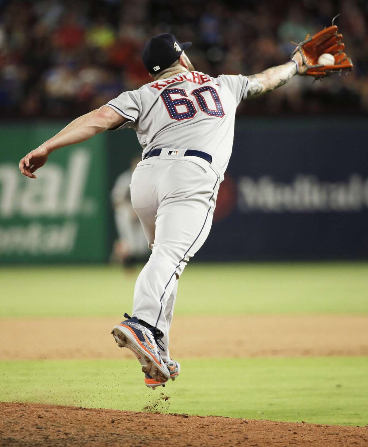 Houston Astros starting pitcher Dallas Keuchel (60) spins to catch a hit by Texas Rangers' Elvis Andrus (1) during the fifth inning of a baseball game, Tuesday, July 3, 2018, in Arlington, Texas. Houston won 5-3. (AP Photo/Brandon Wade)