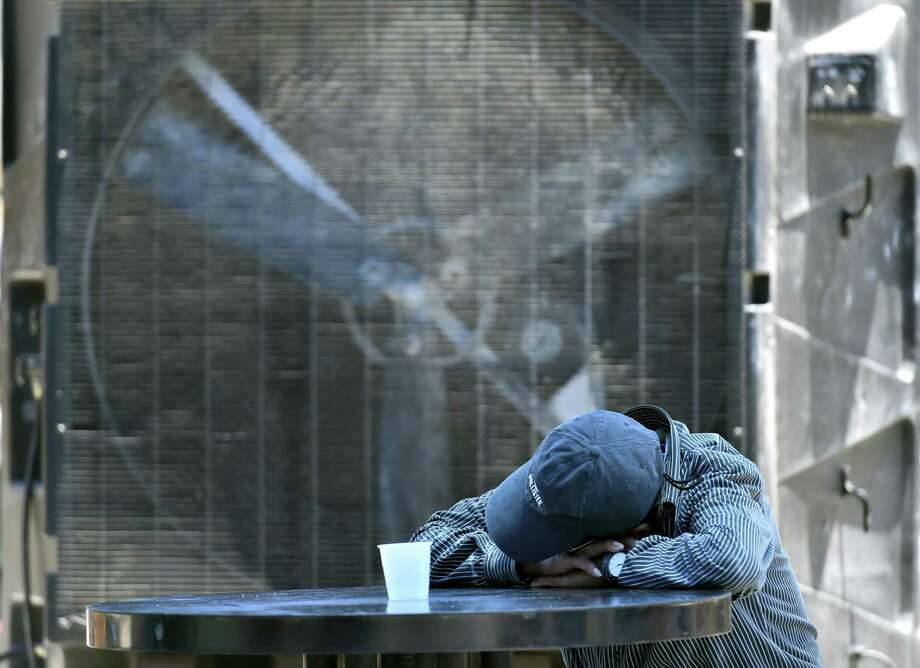 A man dozes in front of a large portable cooler at Haven For Hope's Courtyard facility back in May. San Antonio is bracing for triple-digit highs for the next six days. Photo: Robin Jerstad /San Antonio Express-News / ROBERT JERSTAD