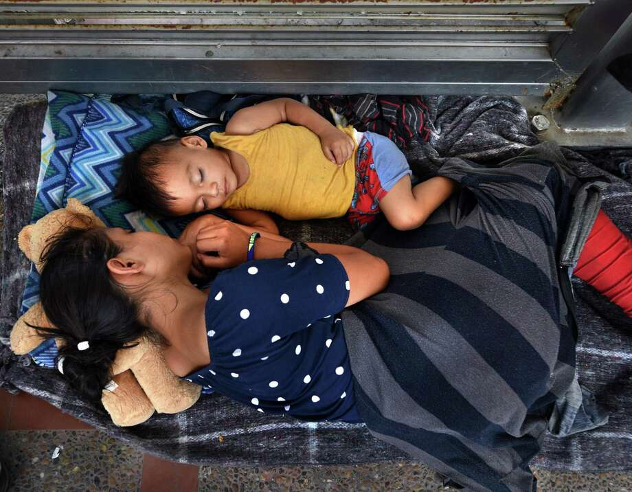 July 2, 2018 - Brownsville, Texas - Asylum seekers sleep on B/M Gateway bridge waiting to cross into U.S. from Mexico side. Ingrid Perdomo, 18 and her 1-year-old son Jose Luis take a nap in blistering heat.  She came with her companion Luis Miguel, 32 from Honduras where they made the difficult 3 month journey.  He said he fled in fear and cries a lot with anxiety about losing his past.  His ex-wife started dating a gang member and the gang torched his home killing his 2 children inside.  He fled to mountains seeking safety where he met Ingrid and they had another child.   When they first arrived they said they were told by border guards they would not get in until their child was an adult, possibly as a deterrent then went to stay with a cousin in Mexico for a few days but had kidnap threats and returned to bridge July 1. They were eventually allowed in late on July 2 to be processed for credible fear. If not for a small humanitarian group Asociacion Civil Ayudandoles a Triunfar a.c. run by Glady Canas from Mexico they would have not had blankets to sleep on, food, water, etc. Carol Guzy/for San Antonio Express-News Photo: Carol Guzy, Freelance / Carol Guzy/for San Antonio Express-News / Carol Gzy