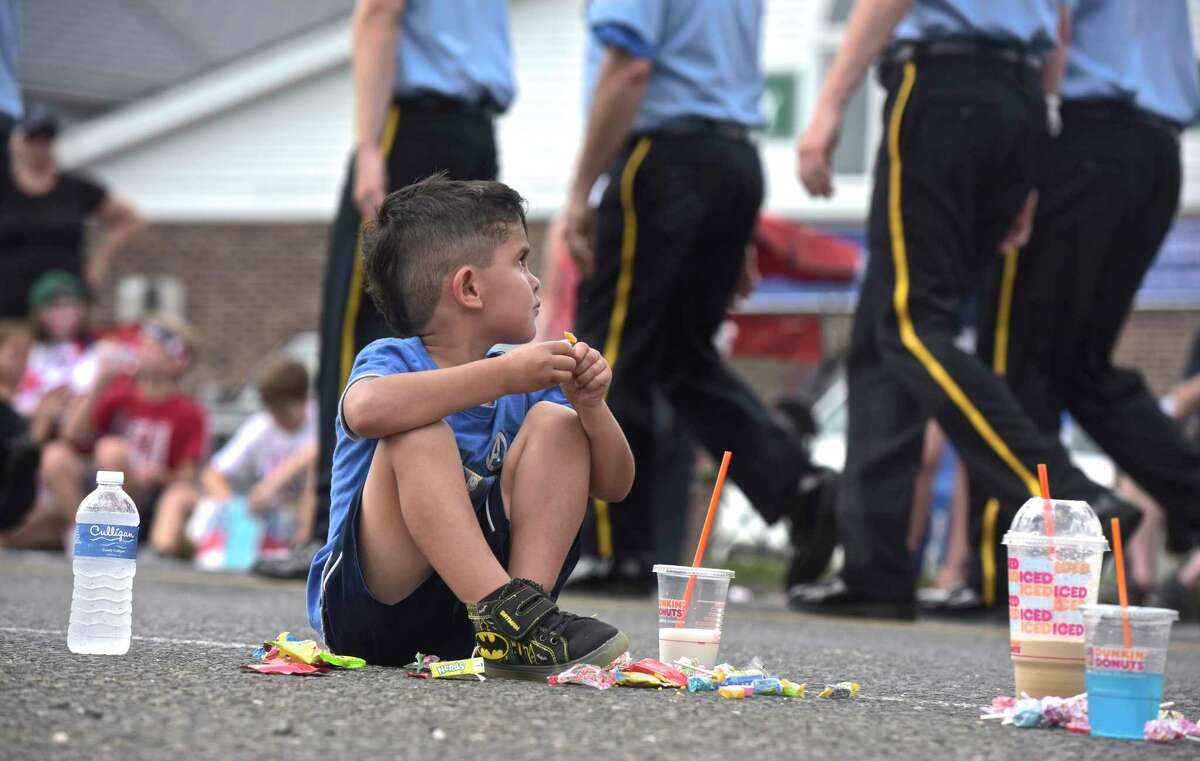 Killian Ortiz-Scalora, 4, of New Fairfield, looks up from counting the stash of candy he collected at the annual Independence Day Parade to watch a fire department march bye. Hosted by the New Fairfield Lions Club. Wednesday, July 4, 2018, in New Fairfield, Conn.