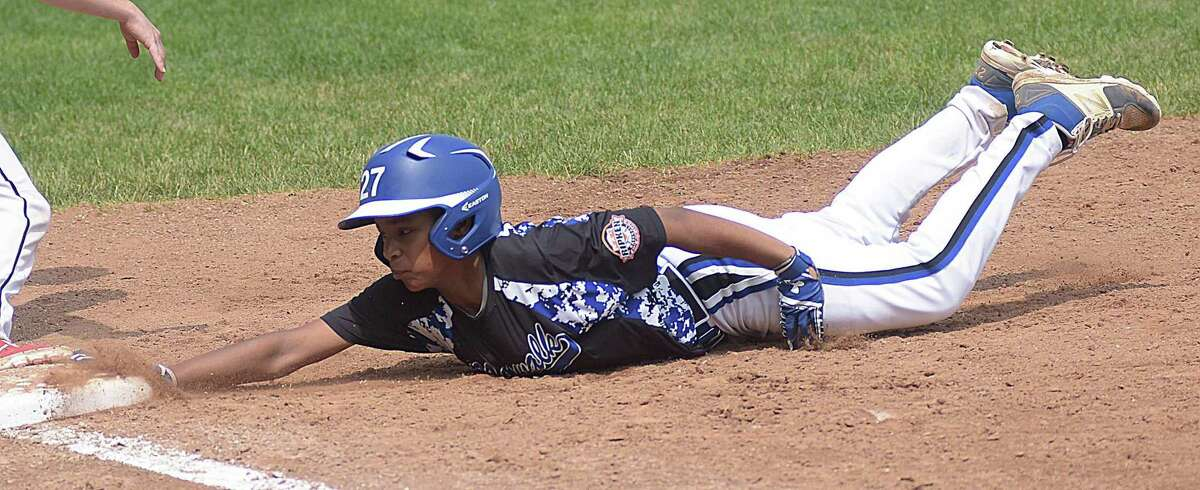 Norwalk's Victoria Ward dives back safely into first on a pick-off attempt during Wednesday's winner's bracket final at the Cal Ripken Baseball 12-year-old state tournament at Devine Field in Norwalk. Norwalk defeated New Canaan 4-1 to advance to the state final for the fourth straight year.