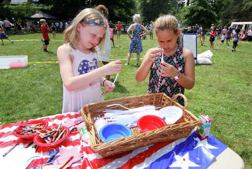 Hannah Perry, 10, and London Lee, 9, right, make bracelets during Pequot Library's annual 4th of July Bike Parade and Lawn Games event in Southport, Conn., on Wednesday July 4, 2018. Chris Frantz, drummer for the Talking Heads, started the event by leading the bike parade from Southport Village on a vintage drum. Afterwards, children took part in a variety of lawn games like a hula hoop contest, a bubble blowing contest, face painting and many other games.