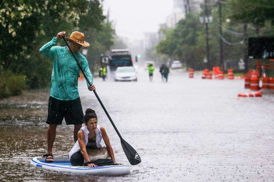 Brady Hewitt navigates his paddle board down South Post Oak Lane as he helps Kim McCormick get to her house as more than eight inches of rain has fallen across parts of the city Wednesday, July 4, 2018 in Houston. Photo: Michael Ciaglo, Houston Chronicle / Michael Ciaglo