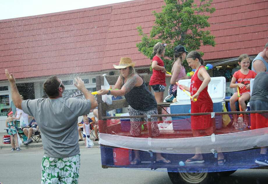 In a last effort to battle the heat, a parade goer gets doused with water during Port Austin's Fourth of July parade on Wednesday. Photo: Seth Stapleton And Bradley Massman/Huron Daily Tribune