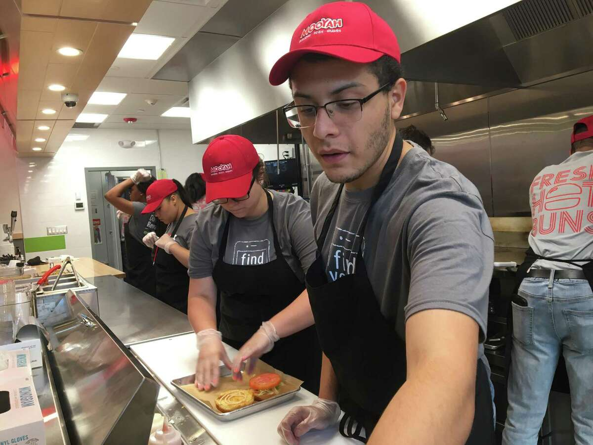 Mooyah Burgers employees make sandwiches at the chain's West Haven location.