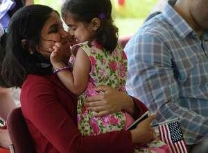Divya Kurthakoti Chandrashekhara from Niskayuna holds her daughter, Anita Simha, 3, before taking her oath of allegiance at a citizenship ceremony at the Saratoga Battlefield on Wednesday, July 4, 2018, in Stillwater, N.Y.  (Paul Buckowski/Times Union)