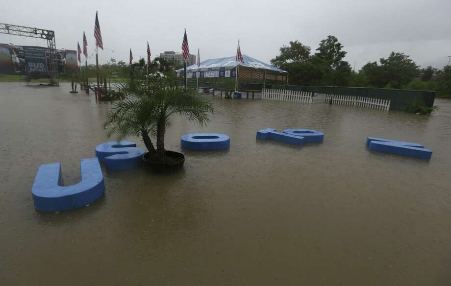 "The ""Houston"" letter signs are floating away from the Budlight beach volleyball court as the water from Buffalo Bayou flooded Eleanor Tinsley Park on Wednesday, July 4, 2018, in Houston. Freedom Over Texas concert is cancelled due to the rain storm and flood of the location. ( Yi-Chin Lee / Houston Chronicle ) Photo: Yi-Chin Lee, Staff Photographer / Houston Chronicle / © 2018 Houston Chronicle"