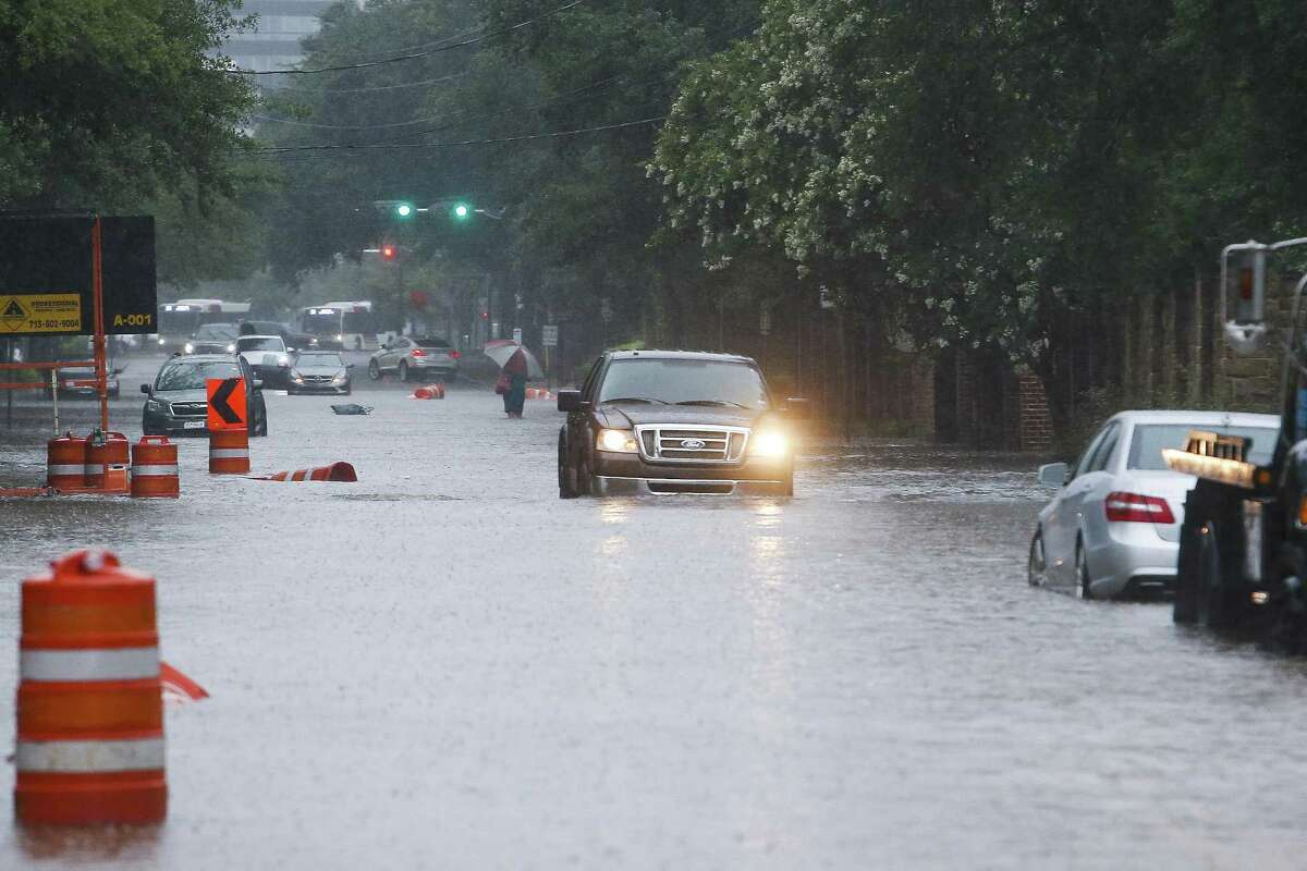 A car drives through flood waters on South Post Oak Lane after more than eight inches of rain has fallen across parts of the city Wednesday, July 4, 2018 in Houston.