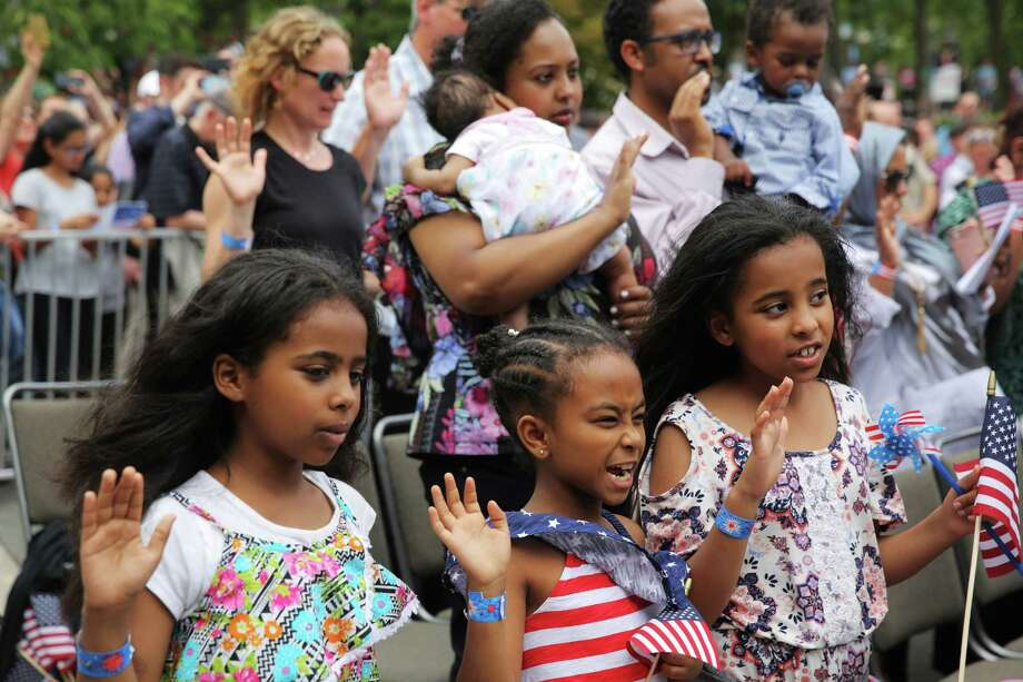 The Dilsebo and Aman families from Ethopia and their combined six children stand to recite the Oath of Citizenship as they and 498 total candidates from 84 different countries become American citizens during the Independence Day Naturalization Ceremony at Seattle Center, Wednesday, July 4, 2018. Photo: GENNA MARTIN, GENNA MARTIN, SEATTLEPI / SEATTLEPI.COM
