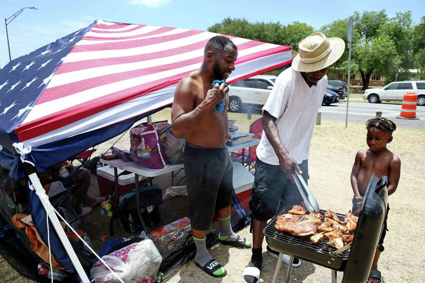 Antwan Love (left) brings his crew out in the heat to turn the barbecue meat during the City's official Fourth of July celebration at Woodlawn Lake on July 4, 2018. Darrell Scroggins takes a turn while Armani Love watches.