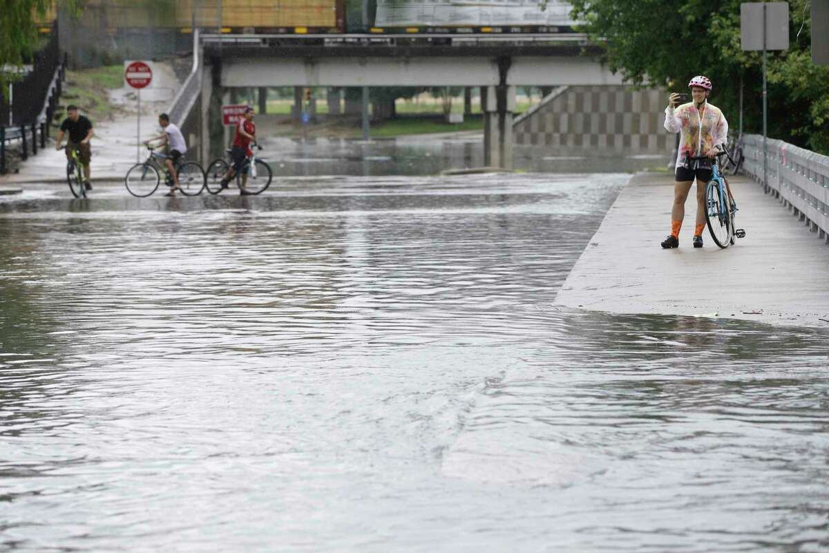 Bicyclists look at the flood water along Milam St. near the intersection of Commerce St. Wednesday, July 4, 2018, in Houston.