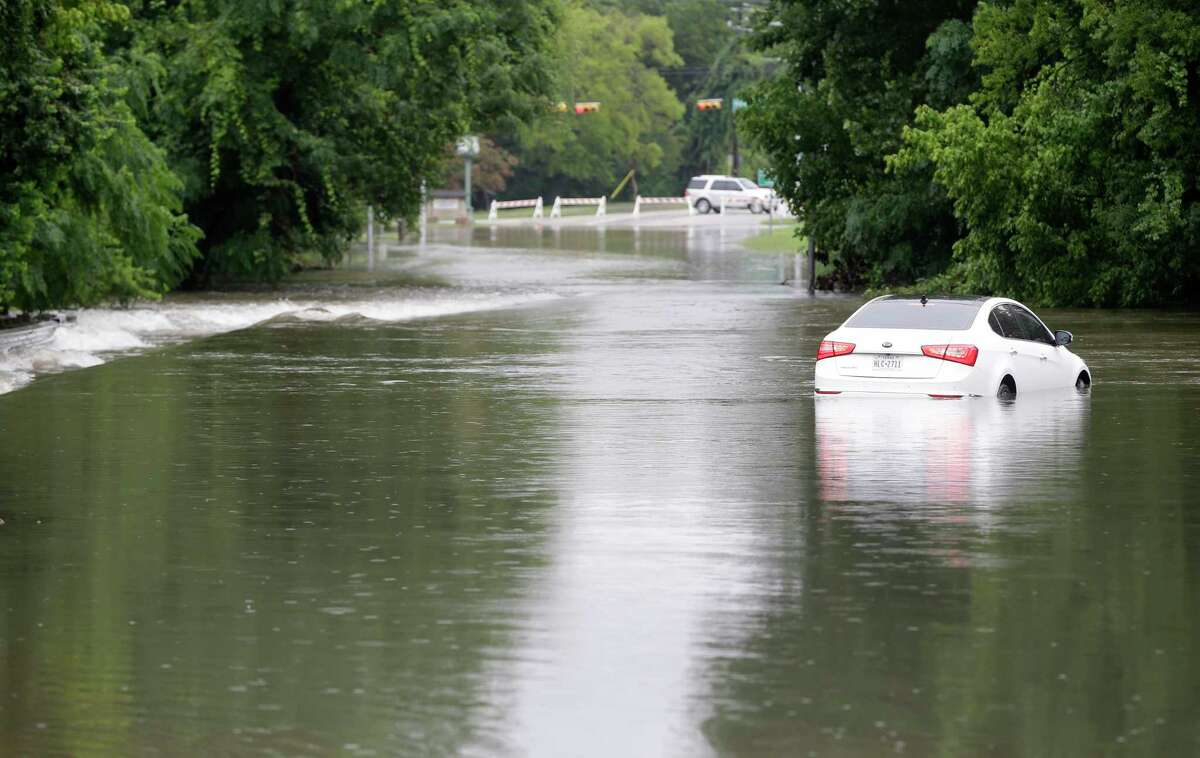 A car is shown stranded on White Oak Dr. near Houston Ave. in the flood water from White Oak Bayou Wednesday, July 4, 2018, in Houston.