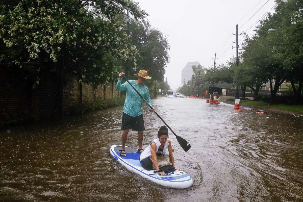 Brady Hewitt navigates his paddle board down South Post Oak Lane as he helps Kim McCormick get to her house as more than eight inches of rain has fallen across parts of the city Wednesday, July 4, 2018 in Houston.