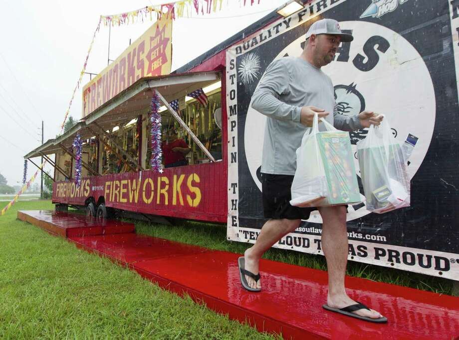 Coulton Woods carries fireworks to his car as rain comes down at a fireworks stand on FM 242 on Wednesday, July 4, 2018, in Conroe. Photo: Jason Fochtman, Staff Photographer / Houston Chronicle / © 2018 Houston Chronicle