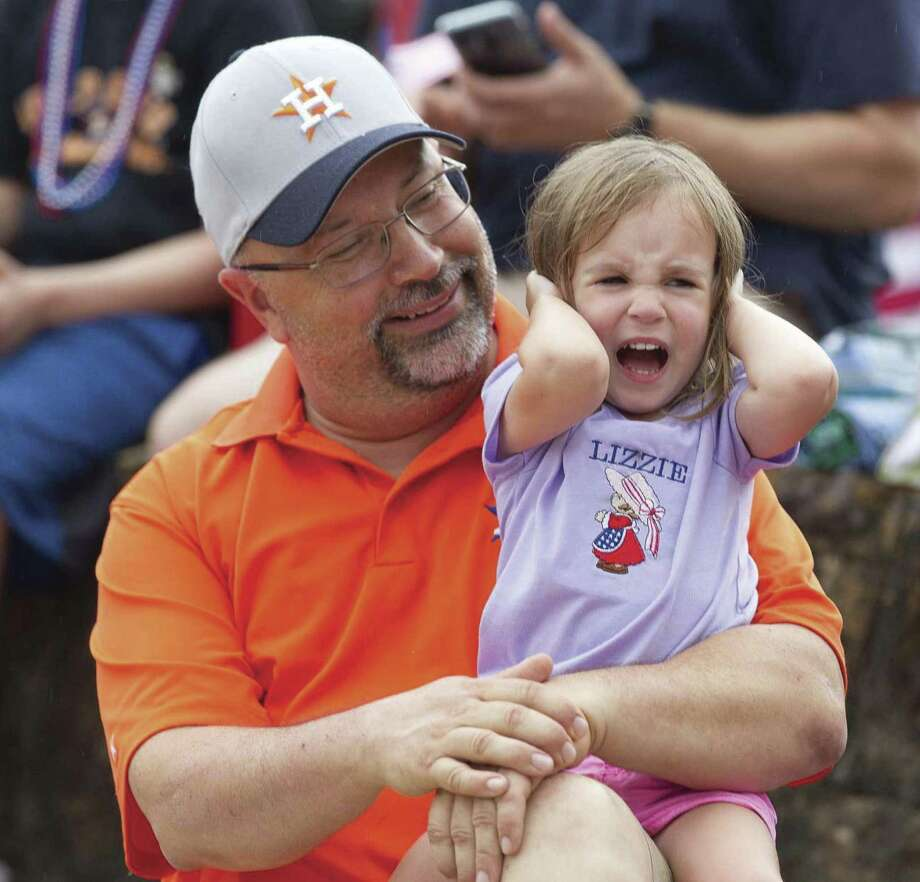 Elizbeth Puffer yells as she covers her ears from loud music as her father Frank holds her during the annual Freedom Fest on Wednesday, July 4, 2018, in Montgomery.
