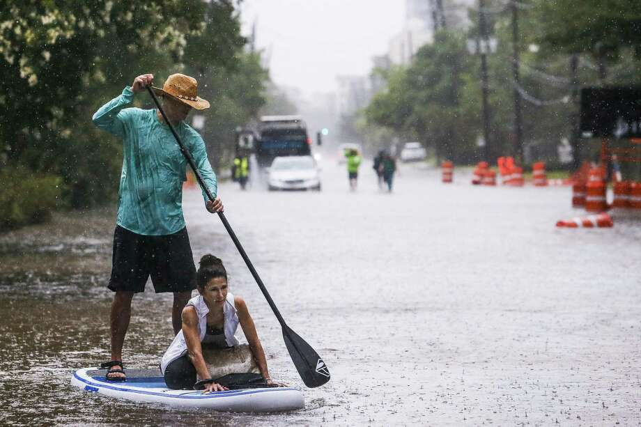 Brady Hewitt navigates his paddle board down South Post Oak Lane in Houston as he helps Kim McCormick get to her house. More than 7 inches of rain fell in parts of Houston on Wednesday. Photo: Michael Ciaglo /Houston Chronicle / Michael Ciaglo