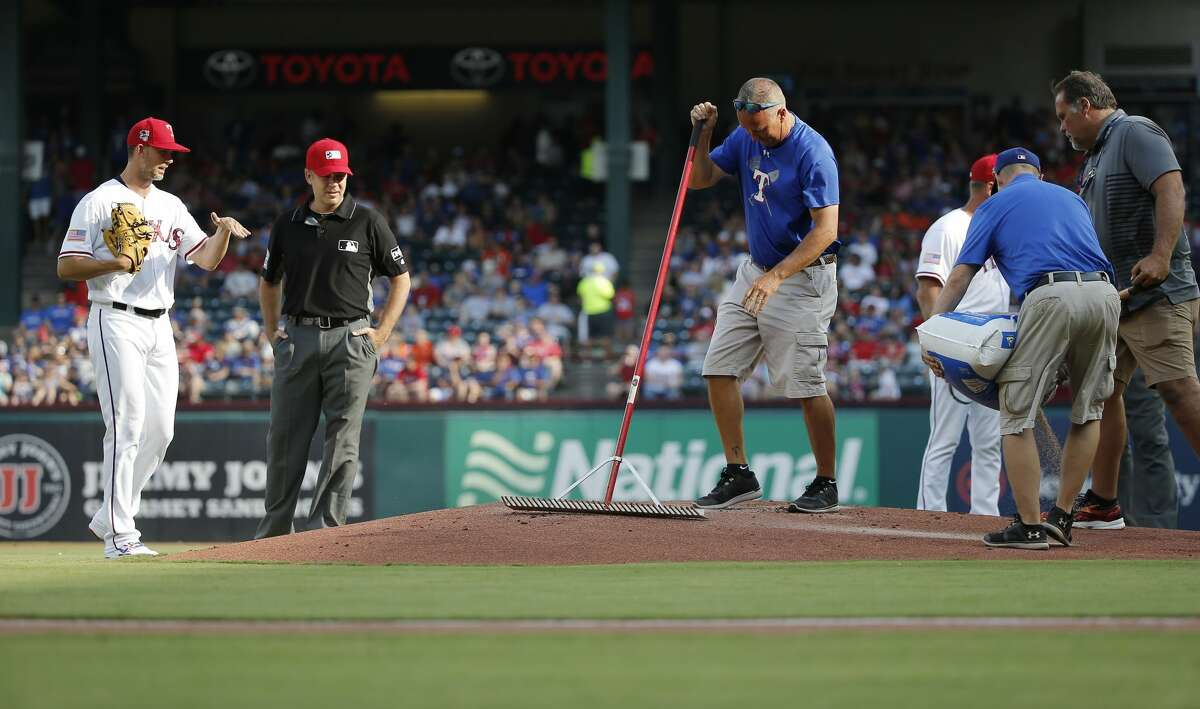 Texas Rangers starting pitcher Mike Minor (36) discusses the condition of the pitcher's mound with second base umpire James Hoye (92) as the grounds crew works on the mound, Wednesday, July 4, 2018, in Arlington, Texas. The game was delayed about 10 minutes. (AP Photo/Brandon Wade)