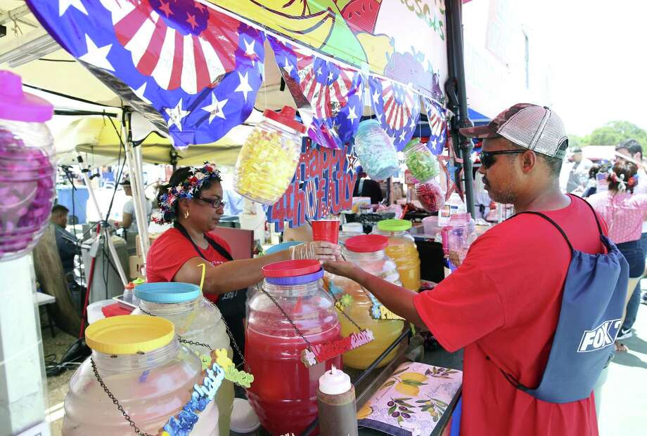 Amira Gallegos serves up a fruit drink to Gregory Wilson at the Lefty's Fresh Fruit booth at Woodlawn Lake on July 4. Photo: Tom Reel /San Antonio Express-News / 2017 SAN ANTONIO EXPRESS-NEWS
