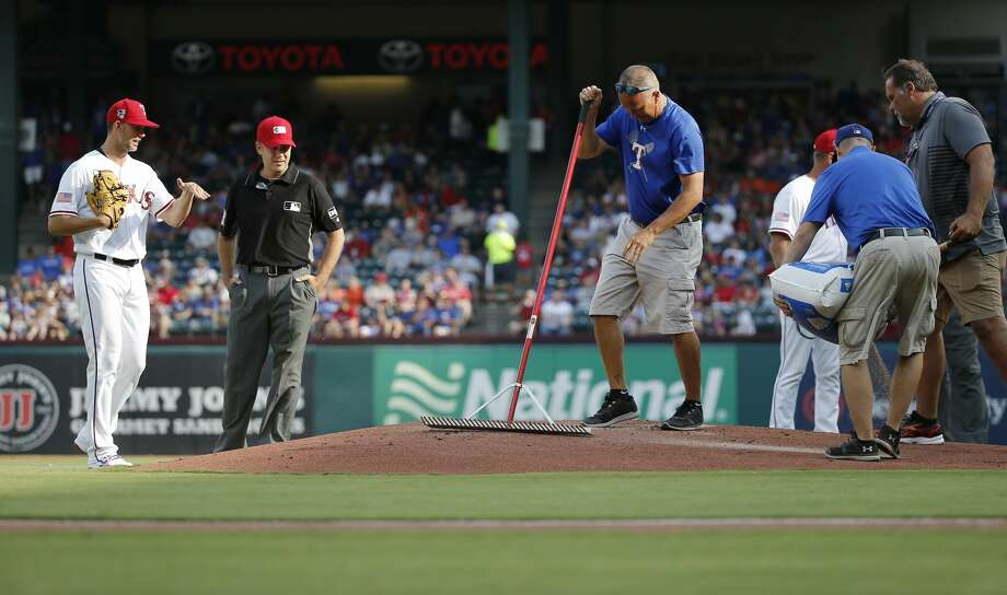 Texas Rangers starting pitcher Mike Minor (36) discusses the condition of the pitcher's mound with second base umpire James Hoye (92) as the grounds crew works on the mound, Wednesday, July 4, 2018, in Arlington, Texas. The game was delayed about 10 minutes. (AP Photo/Brandon Wade) Photo: Brandon Wade/Associated Press