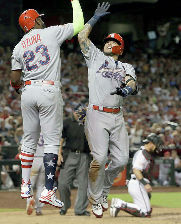 The Cardinals' Yadier Molina celebrates with Marcell Ozuna (23) after hitting a three-run home run in the seventh inning of Wednesday night's game in Phoenix. Photo:       AP