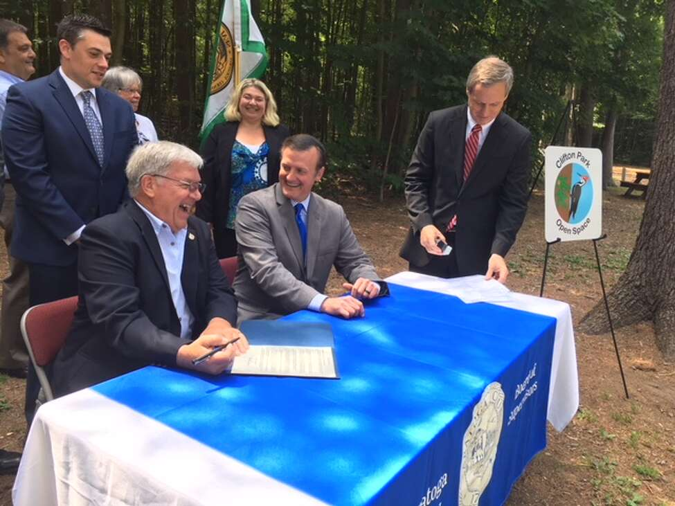 Saratoga County Board of Supervisors Chairman Ed Kinowski and Clifton Park Town Supervisor Phil Barrett sign the paperwork transferring Kinns Road Park to the Town of Clifton Park on June 21. Barrett was instrumental in stopping a logging operation in 2015.