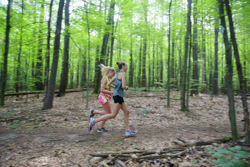 Julia Zachgo, left, and Hannah Reale work out together during a training session with the Outliers Girls Running Club at Kinns Road Park. Shenendehowa track runner beat the heat in the summer working out in the park shaded by tall pines. (Paul Buckowski / Times Union)