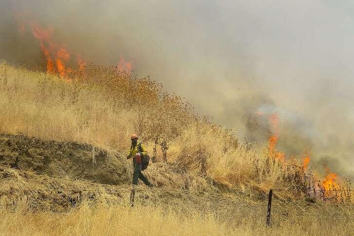 Hot Shot crews from Mendocino use backfires to help contain the County Fire along Highway 129 near Lake Berryessa in Yolo County, California, Tuesday, July 3, 2018. (Randall Benton/The Sacramento Bee via AP)